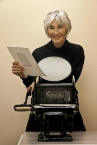 Founder Cathy DeForest with antique printing press