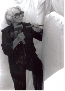 Artist and sculptor, J. Ellen Austin with hammer and chisel against a stone as large as herself of Italian Translucent Alabaser for an installation