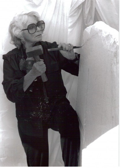Artist and sculptor, J. Ellen Austin with hammer and chisel against a stone as large as herself of Italian Translucent Alabaster for an installation