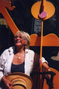 J. Ellen, Sculptor, poses with a lifesize wooden sculpture of a whimsical bimbo in yellow