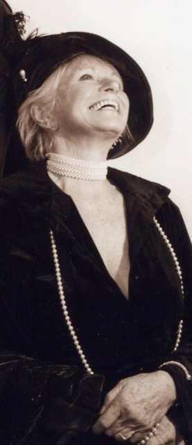 sepia photo of J. Ellen looking up and smiling in great joy wearing a black hat with a feather in a pearl choker necklace and a long strand of pearls with a black long sleeved shirt down to her crossed hands, A lovely attitude